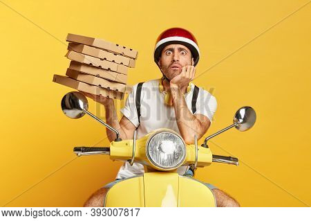Photo Of Male Courier Has Fearful Expression, Holds Pile Of Cardboard Boxes Filled With Pizza, Deliv