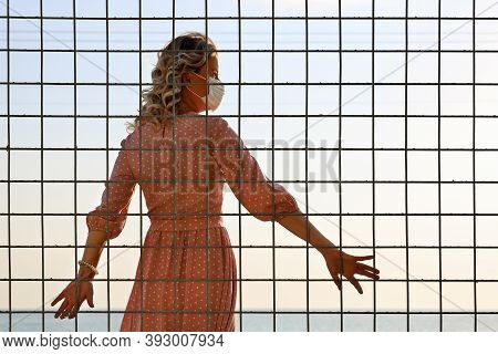 Young Woman Wearing Protective Face Mask Stands With Her Back To The Square Lattice And Looks Toward