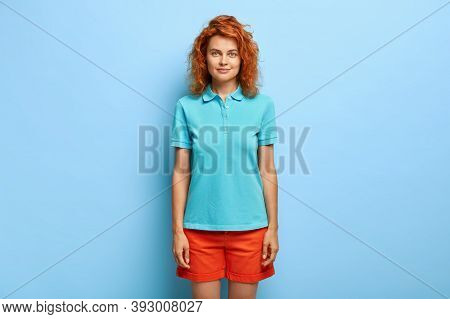Studio Shot Of Pleasant Looking Young Ginger Girl Has Wavy Hair, Looks Directly At Camera, Wears Blu