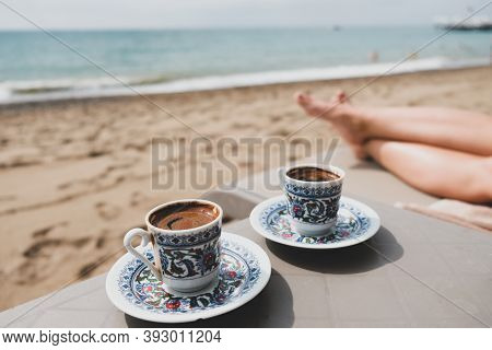 Luxury Beach Vacation For Couple In Turkey. Two Cups Of Turkish Coffee, Female Legs, Sand And Medite