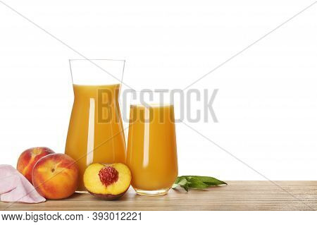 Freshly Made Tasty Peach Juice On Wooden Table Against White Background