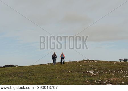 Mendip Hills, Uk - October 07, 2020: Senior Couple With Walking Sticks Hiking Up The Hill In The Men