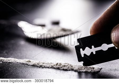 Hand Separating With A Blade A Portion Of Cocaine, White Powder To Be Inhaled, Concept Of Addiction