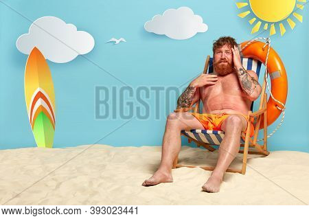 Frustrated Red Haired Man Sunbathes At Sandy Beach, Has Headache After Sunstroke, Wears Orange Short