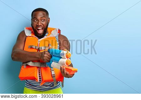 Positive Playful Dark Skinned Man Has Real Struggle, Holds Water Gun, Shoots In Someone, Dressed In