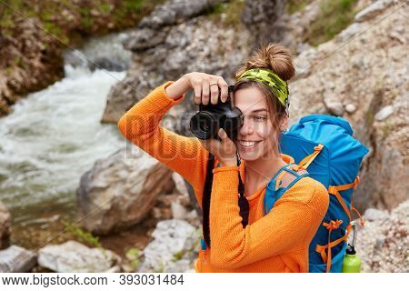 Young Female Adventurer Poses Against Small River In Ravine, Holds Camera, Takes Picture Of Landscap