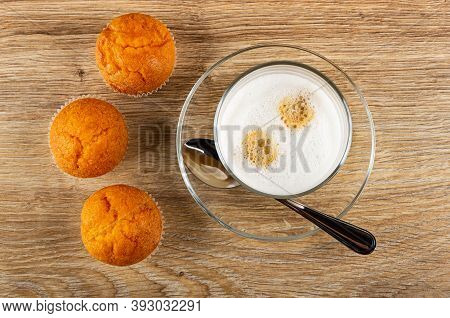Three Orange Muffins, Transparent Glass With Latte-macchiato, Teaspoon On Saucer On Wooden Table. To
