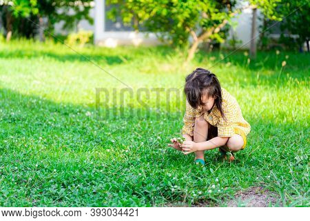 Girl In Yellow Dress Was Picking Up The Grass Flower. Children Squatting On The Green Lawn In An Eve