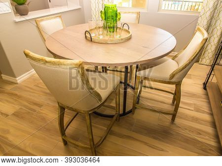 Dining Area With Round Wooden Table, Four Chairs & Centerpiece