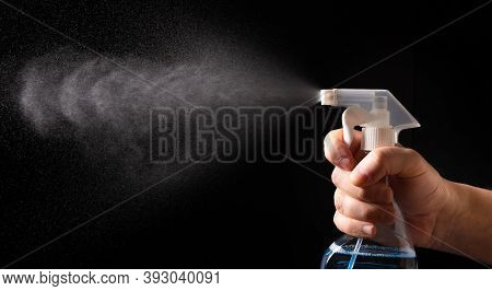 On A Black Background, A Hand With A Spray Bottle. A Spray Of Water. Antibacterial Gel For Hand Disi