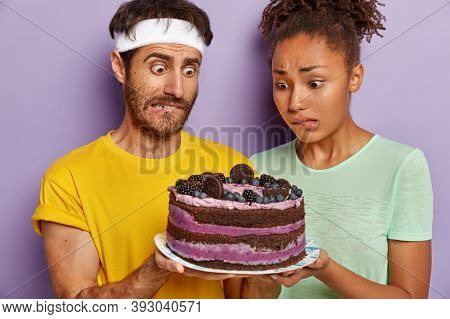 Puzzled Husband And Wife Stare With Big Appetite At High Energy Cake, Bite Lips, Have Desire To Eat,