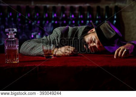 Alcohol Addiction And People Concept - Man Alcoholic With Glass Of Whiskey And Bottle Lying Or Sleep