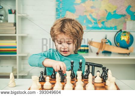 Happy Child And Childhood. Chess Strategy. Kid Playing Chess. Concentrated Boy Developing Chess Stra