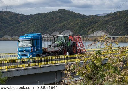 Agricultural Equipment - Tractor - Transported On The Street, On The Car Platform.cross A Bridge. Ca