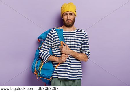 Upset Dejected Hitchhiker Poses With Big Rucksack, Dressed In Striped Sailor Jumper, Tired After Lon