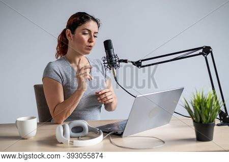 A Charming Woman Radio Host Is Broadcasting Live On A Laptop. Online Radio Concept
