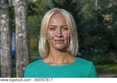 Street Portrait Of A Young Woman 25-30 Years Old On The Background Of Nature, Happy Expression,