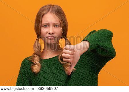 Image Of Pretty Blonde Girl 12-14 Years Old In Warm Green Sweater Showing Thumb Down. Unlike, Dislik