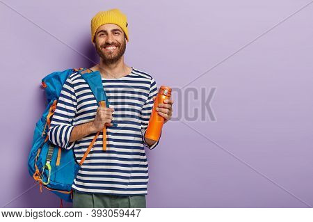 Smiling Delighted Male Tourist Has Awesome Trip, Carries Big Rucksack, Drinks Coffee From Flask, Bei