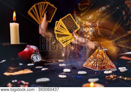 Astrology And Esotericism. Magic Glass Pyramid With A Magical Glow. In The Background, A Fortune Tel