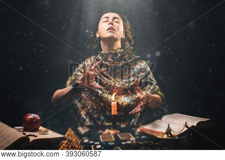Astrology, Magic And Divination. The Sorceress Creates The Magic Of Divination Over A Candle. Black