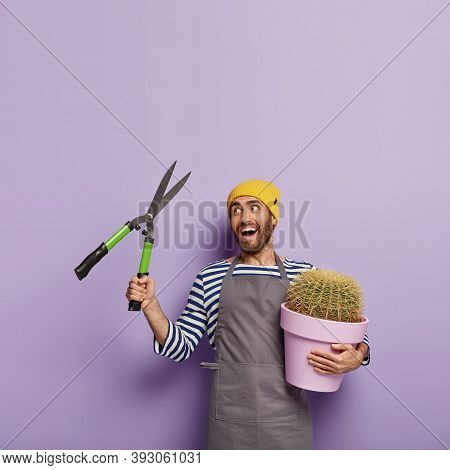 Indoor Shot Of Happy Gardener Takes Care About Growning Pot Plant, Holds Gardening Shears, Going To
