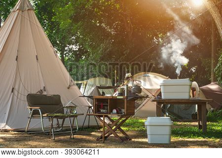 Outdoor Kitchen Equipment And Wooden Table Set With Field Tents Group In Camping Area At Natural Par