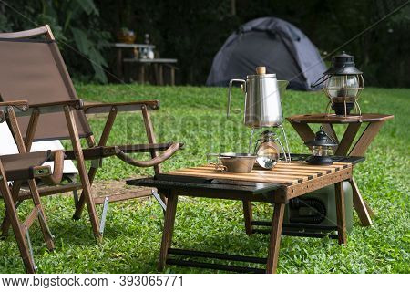 Stainless Steel Kettle, Portable Gas Stove, Bowl And Vintage Lanterns With Outdoors Table Set On Gre