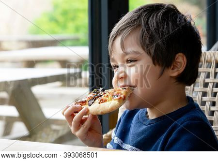 Cropped Shot Cute Kid Boy Eating Home Made Pizza In The Cafe,  Happy Young Boy Biting Off Big Slice