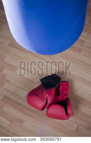 A Pair Of Punching Gloves And Boxing Bag