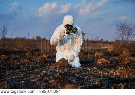 Male Ecologist In Protective Suit And Gas Mask Pouring Out Soil From His Hand While Doing Research W