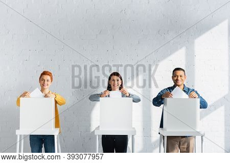 Multicultural Voters Inserting Ballots Into Polling Boxes Against White Brick Wall