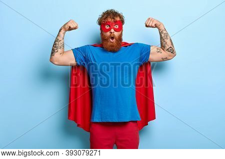 Confident Red Head Male Superhero Wears Mask And Red Cape, Raises Arms, Shows Muscles, Represents Po
