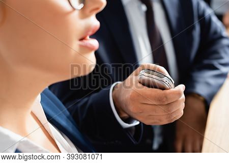 Partial View Of Journalist With Dictaphone Interviewing Politician During Press Conference, Blurred