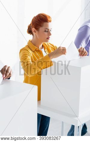 Woman Inserting Bulletin Into Polling Box Near Voters On Blurred Background