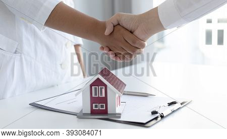Property manager Shake hands with congratulations on the customers who bought the house with insuran