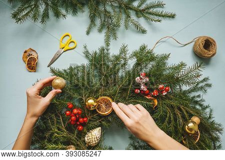 Christmas Composition. Woman Making Handmade Christmas Wreath. Top View, Flat Lay. Blue Background,
