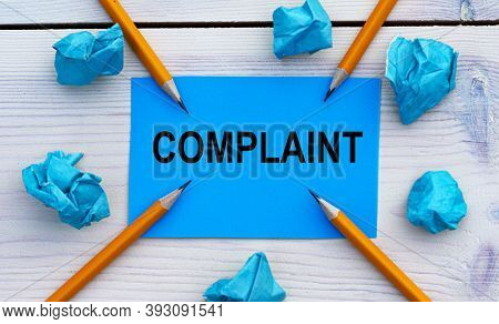 Complaint - Word On Blue Paper On A Light Background With Crumpled Pieces Of Paper And Pencils. Busi