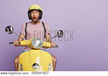 Isolated Shot Of Thoughtful Shocked Driver Drives Motorbike, Wears Protective Headgear, Forgets Abou