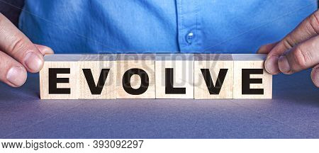The Word Evolve Is Made Up Of Wooden Cubes By A Man. Business Concept