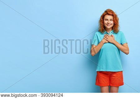 Pretty Ginger Girl Has Positive Smile, Touches Chest With Both Hands Makes Gratitude Gesture Gazes T
