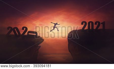 Surreal View, Man Jumping Over A Chasm Obstacle Between Old 2020 And New 2021 Years. Self Overcome,
