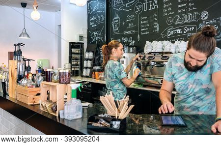 Young Waitress Preparing The Coffee Machine While Her Coworker Uses The Tablet