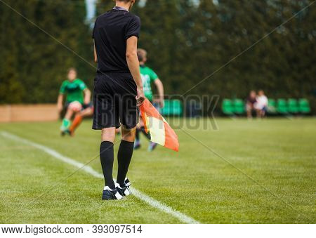 Young Football Referee On Sideline Holding Flag. Junior Level Soccer Players Compete In Tournament M