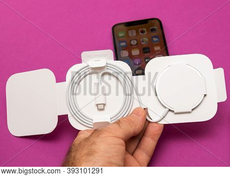 Paris, France - Nov 2, 2020: Man Hand Holding New Magsafe By Apple Computers A Proprietary Magnetica