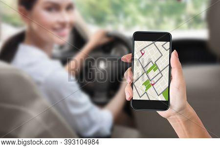 Female Hand Holding Smartphone With Car Navigation App On Screen, While Woman Driving Automobile In