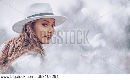 Happy christmas mood. Beautiful young woman in hat is enjoying the snowfall in the winter park. Winter weather.
