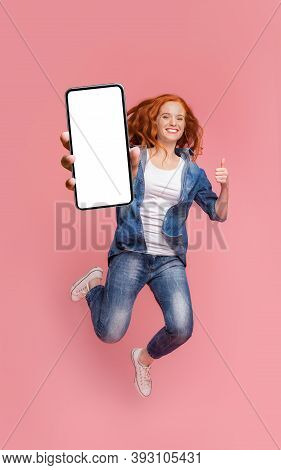 Cheerful Girl Redhead Teenager Jumping Up, Showing Thumb Up And Newest Smartphone With Empty Screen,