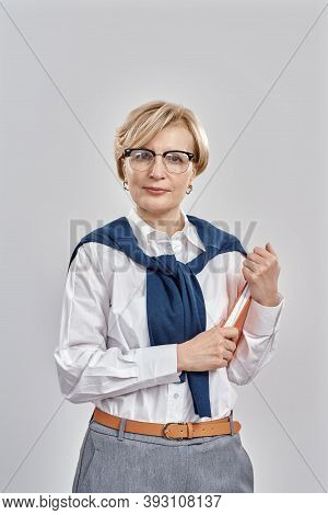 Portrait Of Elegant Middle Aged Caucasian Woman Wearing Business Attire And Glasses Looking At Camer