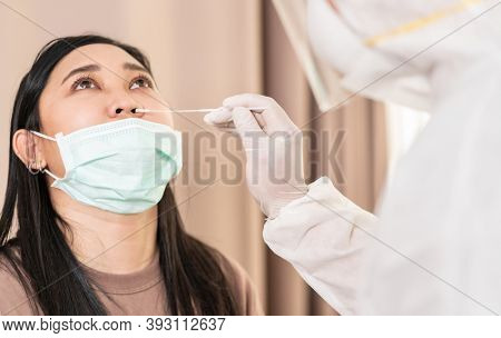 Medical staff with PPE suit test coronavirus covid-19 to asian woman by nose swab at hospital. COVID-19 testing health care concept.